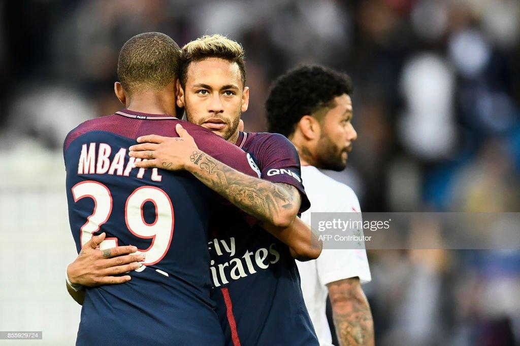 Paris Saint-Germain's Brazilian forward Neymar (C) and Paris Saint-Germain's French forward Kylian Mbappe embrace after the French L1 football match Paris Saint-Germain (PSG) vs Bordeaux (FCGB) on September 30, 2017 at the Parc des Princes stadium in Paris. /