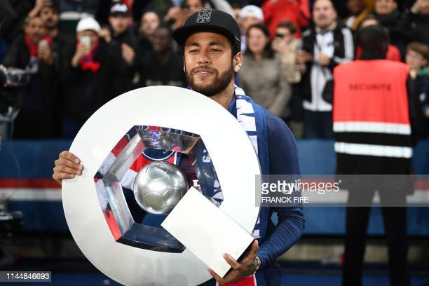 Paris Saint-Germain's Brazilian forward Neymar celebrates with the champion's trophy at the end of the French L1 football match between Paris...
