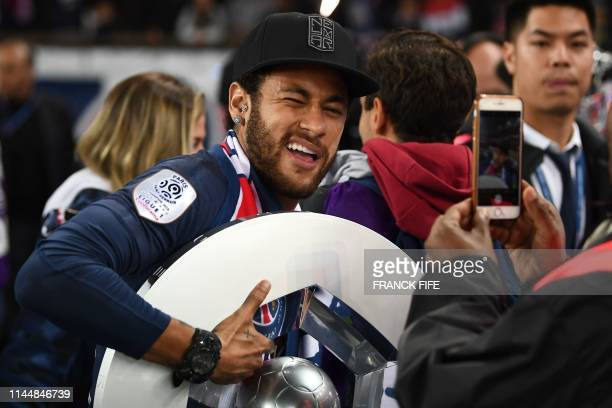 TOPSHOT Paris SaintGermain's Brazilian forward Neymar celebrates with the champion's trophy at the end of the French L1 football match between Paris...