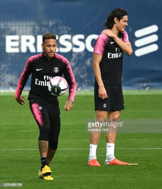 Paris SaintGermain's Brazilian forward Neymar controls the ball bext to Paris SaintGermain's Uruguayan forward Edinson Cavani during a training...