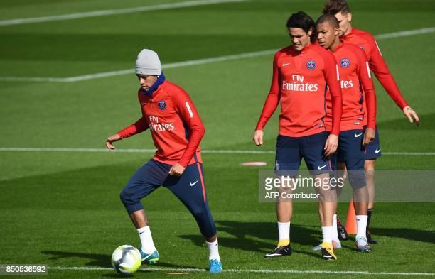 Paris SaintGermain's Brazilian forward Neymar controls the ball netx to Paris SaintGermain's Uruguayan forward Edinson Cavani and Paris...