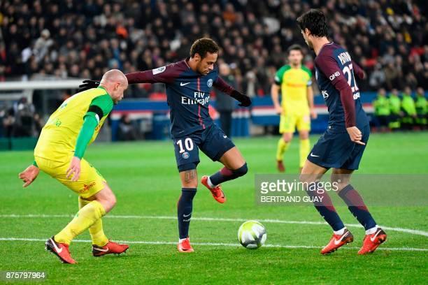 Paris SaintGermain's Brazilian forward Neymar controls the ball between Nantes' French defender Nicolas Pallois and Paris SaintGermain's Argentinian...