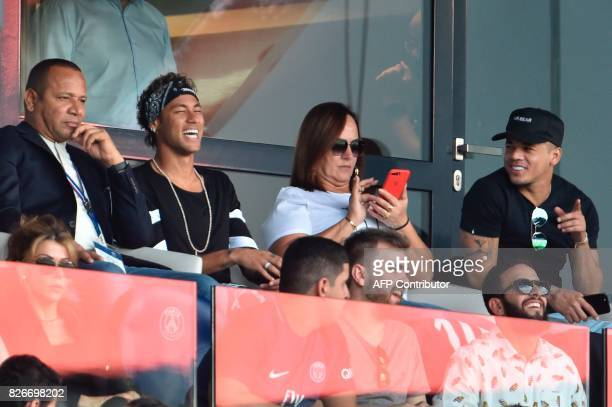 Paris SaintGermain's Brazilian forward Neymar flanked by his father Neymar Santos mother Nadine Santos and a close friend Jo Amancio reacts during...