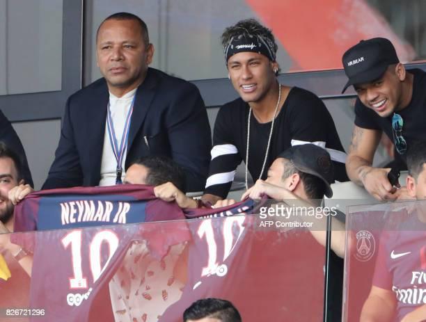 Paris SaintGermain's Brazilian forward Neymar flanked by his father Neymar Santos and a close friend Jo Amancio watches the French L1 football match...