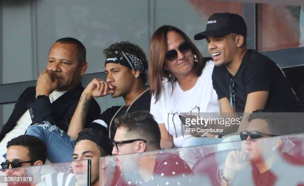 Paris SaintGermain's Brazilian forward Neymar flanked by his father Neymar Santos his mother Nadine Santos and a close friend Jo Amancio reacts as he...