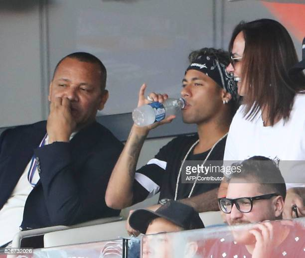 Paris SaintGermain's Brazilian forward Neymar flanked by his father Neymar Santos and his mother Nadine Santos drinks as he watches the French L1...
