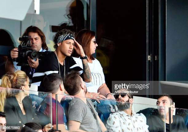 Paris SaintGermain's Brazilian forward Neymar flanked by his mother Nadine Santos reacts as he attends the French L1 football match between Paris...