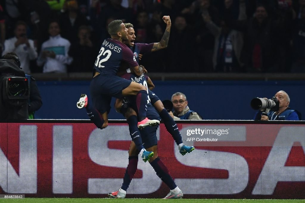 Paris Saint-Germain's Brazilian forward Neymar (C) is congratulated by Paris Saint-Germain's Brazilian defender Dani Alves and Paris Saint-Germain's French forward Kylian Mbappe after he scored a goal during the UEFA Champions League football match between Paris Saint-Germain and Bayern Munich on September 27, 2017 at the Parc des Princes stadium in Paris. /
