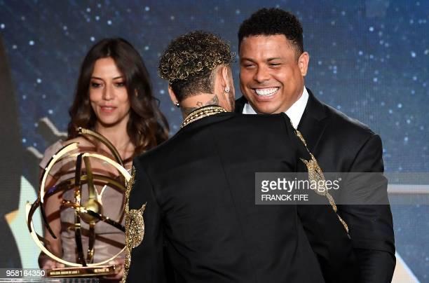 Paris SaintGermain's Brazilian forward Neymar is congratulated by former Brazilian football star ROnaldo as he receives the Best Ligue 1 Player award...