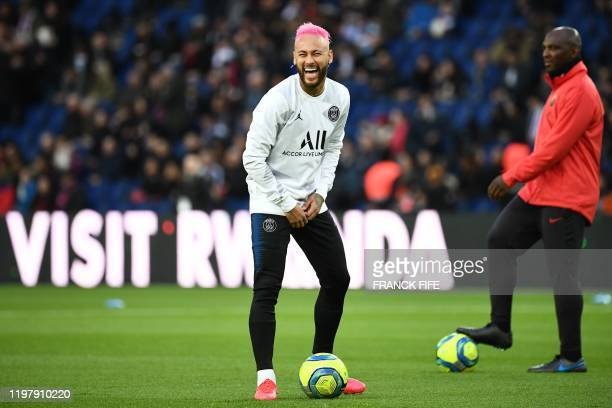 Paris Saint-Germain's Brazilian forward Neymar laughs during warm up prior to the French L1 football match between Paris Saint-Germain and...