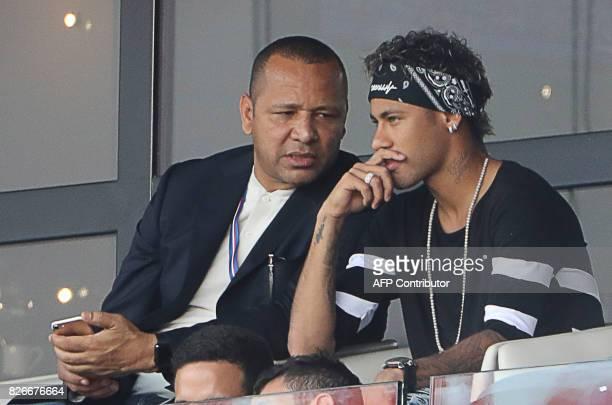 Paris SaintGermain's Brazilian forward Neymar listens to his father Neymar Santos as they watch the French L1 football match between Paris...