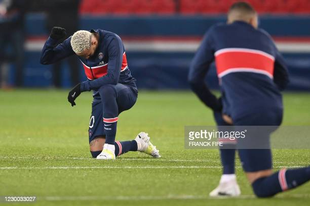 Paris Saint-Germain's Brazilian forward Neymar , other players and referees kneel on the pitch against racism before the UEFA Champions League group...