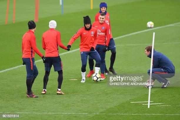 Paris SaintGermain's Brazilian forward Neymar plays the ball next to di Paris SaintGermain's Argentinian forward Angel Di Maria next to Paris...