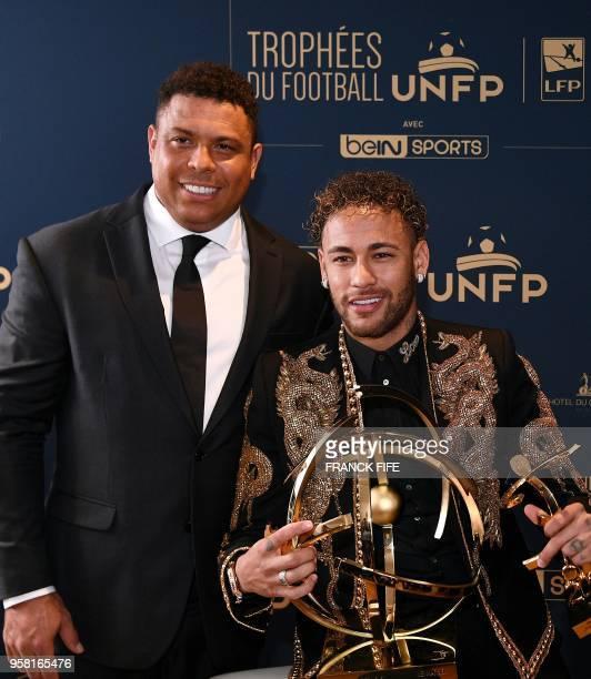 Paris SaintGermain's Brazilian forward Neymar poses with his trophy past former Brazilian international player Ronaldo after receiving the Best Ligue...
