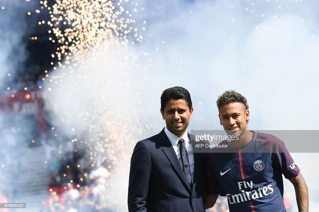 TOPSHOT - Paris Saint-Germain's Brazilian forward Neymar (R) poses with Paris Saint Germain's (PSG) Qatari president Nasser Al-Khelaifi (L) during his presentation to the fans at the Parc des Princes stadium in Paris, on August 5, 2017. Brazil superstar Neymar will watch from the stands as Paris Saint-Germain open their season on August 5, 2017, but the French club have already clawed back around a million euros on their world record investment. Neymar, who signed from Barcelona for a mind-boggling 222 million euros ($264 million), is presented to the PSG support prior to his new team's first game of the Ligue 1 campaign against promoted Amiens. JOCARD