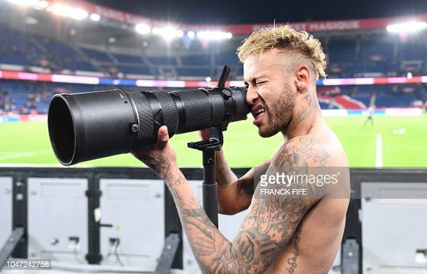 TOPSHOT Paris SaintGermain's Brazilian forward Neymar pretends to take pictures of his team mates as they celebrate winning the French L1 football...