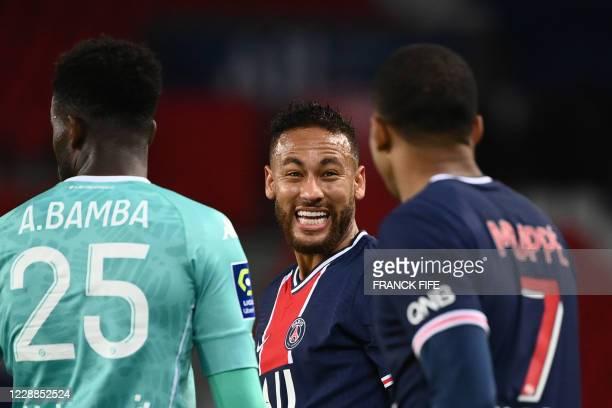 Paris Saint-Germain's Brazilian forward Neymar reacts with Paris Saint-Germain's French forward Kylian Mbappe during the French L1 football match...