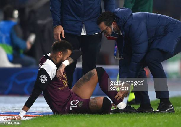 Paris Saint-Germain's Brazilian forward Neymar receives medical treatment from medical staff during the UEFA Champions League Group H football match...