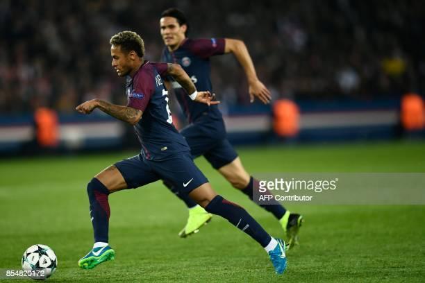 TOPSHOT Paris SaintGermain's Brazilian forward Neymar runs with the ball followed by Paris SaintGermain's Uruguayan forward Edinson Cavani during the...