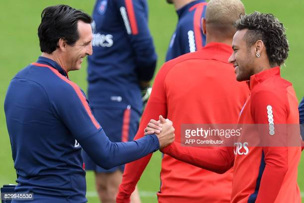 Paris SaintGermain's Brazilian forward Neymar shakes hands with Paris SaintGermain's Spanish head coach Unai Emery during a training session at the...