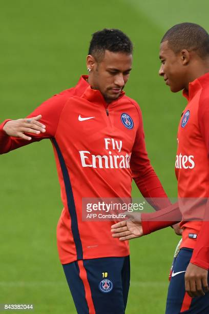 Paris SaintGermain's Brazilian forward Neymar shakes hands with Paris SaintGermain's French forward Kylian Mbappe during a training session at the...
