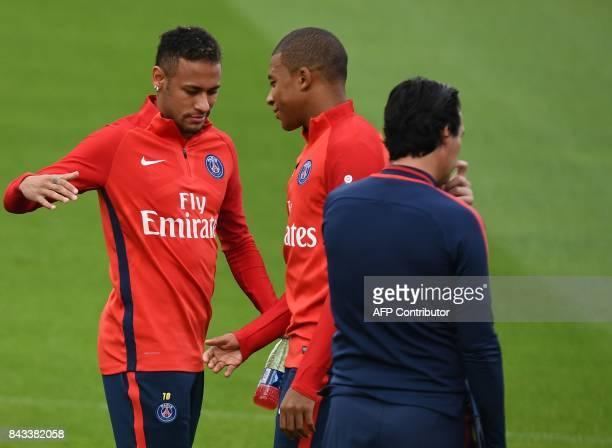 Paris SaintGermain's Brazilian forward Neymar shakes hands with Paris SaintGermain's French forward Kylian Mbappe next to Paris SaintGermain's...