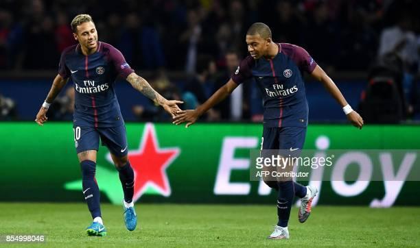 Paris SaintGermain's Brazilian forward Neymar shkae shands of Paris SaintGermain's French forward Kylian Mbappe after scoring a goal during the UEFA...