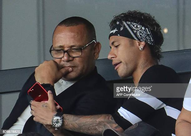 Paris SaintGermain's Brazilian forward Neymar shows his father Neymar Santos something on his mobile phone during the French L1 football match...