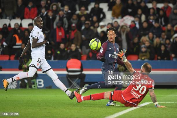 Paris SaintGermain's Brazilian forward Neymar slips the ball past Dijon's French goalkeeper Baptiste Reynet for Paris SaintGermain's Argentinian...