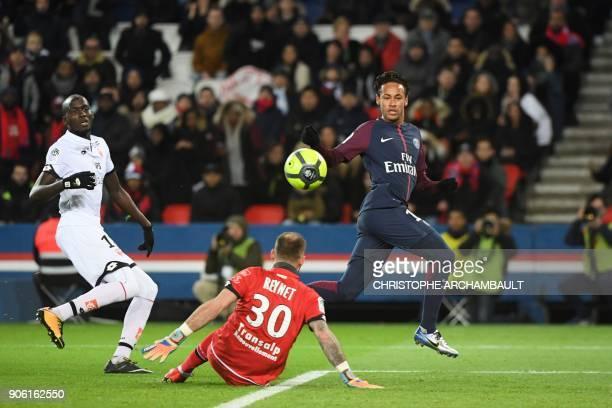 Paris SaintGermain's Brazilian forward Neymar slips the ball past Dijon's French goalkeeper Baptiste Reynet for Paris SaintGermain's Argentinian...
