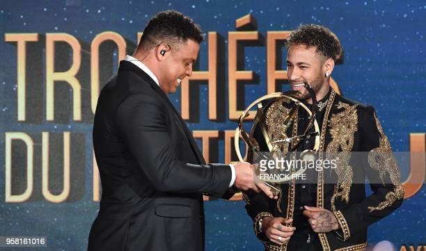 Paris SaintGermain's Brazilian forward Neymar smiles after receiving the Best Ligue 1 Player award from former Brazilian international player Ronaldo...