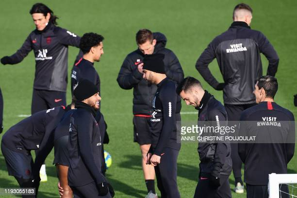 Paris Saint-Germain's Brazilian forward Neymar smiles as he warm up with his teammates during a training session at the club's Camp des Loges...