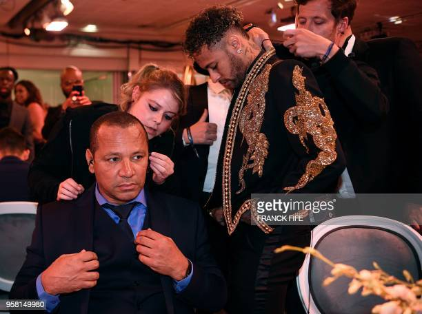 Paris SaintGermain's Brazilian forward Neymar stands past his father Neymar Santos during a TV show on May 13 2018 in Paris as part of the 27th...