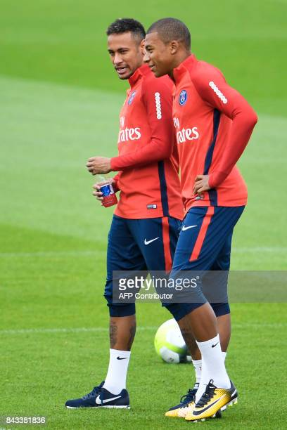 Paris SaintGermain's Brazilian forward Neymar talk to Paris SaintGermain's French forward Kylian Mbappe during a training session at the club's...