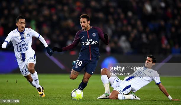 Paris SaintGermain's Brazilian forward Neymar vies with Troyes defender Mathieu Deplagne and Troyes' French defender Christophe Herelle during the...