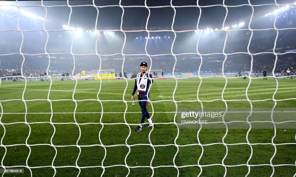 TOPSHOT - Paris Saint-Germain's Brazilian forward Neymar walks on the pitch after winning the French L1 title at the end of the French L1 football match Paris Saint-Germain (PSG) vs Rennes at The Parc des Princes Stadium in Paris on May 12, 2018.