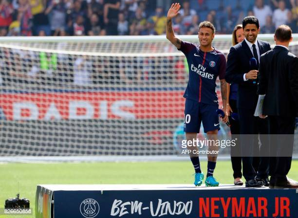 Paris SaintGermain's Brazilian forward Neymar waves to the crowd next to Paris Saint Germain's Qatari president Nasser AlKhelaifi during the player's...