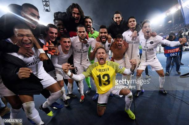 TOPSHOT Paris SaintGermain's Brazilian forward Neymar wearing the jersey of Liverpool's Brazilian goalkeeper Alisson Becker celebrates with teammates...