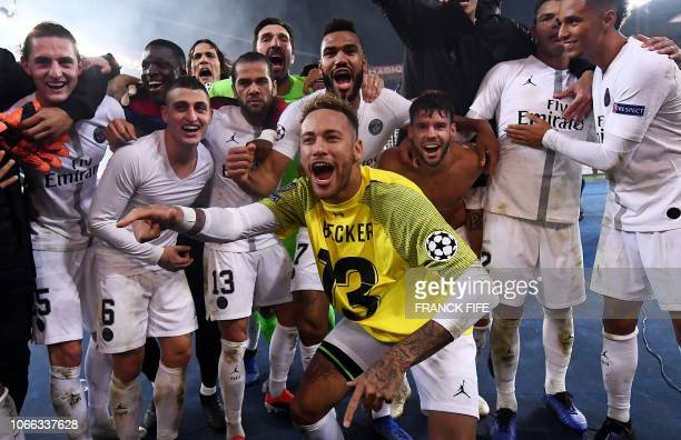Paris SaintGermain's Brazilian forward Neymar wearing the jersey of Liverpool's Brazilian goalkeeper Alisson Becker celebrates with teammates after...