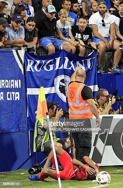 Paris SaintGermain's Brazilian midfielder Lucas Moura lies on the ground after a Bastia's supporter tried to hit him with a stick from the stands...