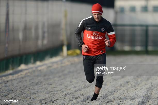 Paris Saint-Germain's British midfielder David Beckham runs in the sand during a training session on February 13, 2013 at the club's Camp des Loges...