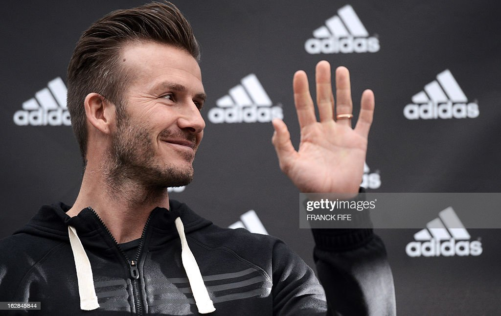 Paris Saint-Germain's (PSG) English midfielder David Beckham waves to the crowd as he takes part in an event for fans in front of a store of his sponsor on the Champs-Elysees avenue in Paris, on February 28, 2013. Beckham and French former international player Zinedine Zidane have autographed balls and jerseys for thirty fans selected via Twitter.