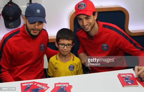 Paris SaintGermain's French defender Layvin Kurzawa and Argentinian midfielder Javier Pastore pose with a fan at a shopping mall in Doha as part of...