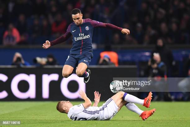 Paris SaintGermain's French defender Layvin Kurzawa jumps over Anderlecht's French midfielder Adrien Trebel during the UEFA Champions League Group B...