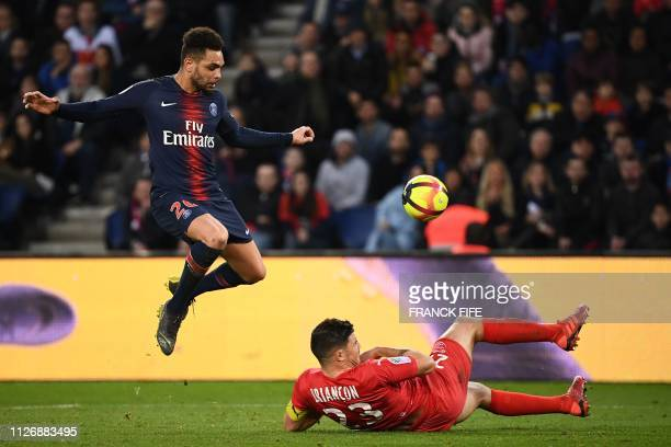 TOPSHOT Paris SaintGermain's French defender Layvin Kurzawa vies with Nîmes' French midfielder Anthony Briancon during the French L1 football match...