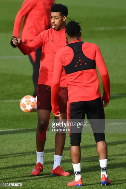 Paris SaintGermain's French defender Presnel Kimpembe chats with a teammate during a training session at the club's Camp des Loges training grounds...