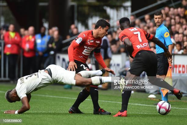 Paris SaintGermain's French defender Presnel Kimpembe falls past Rennes' French midfielder Benjamin Andre during the French L1 football match between...