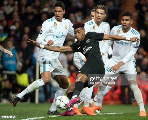 Paris SaintGermain's French defender Presnel Kimpembe kicks the ball beside Real Madrid's French defender Raphael Varane Real Madrid's Portuguese...