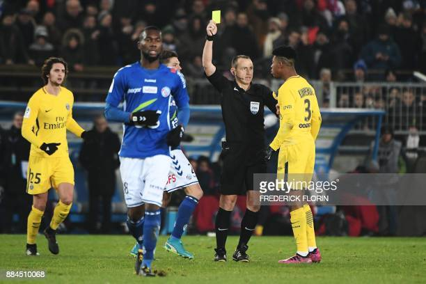 Paris SaintGermain's French defender Presnel Kimpembe receives a yellow card from French referee Ruddy Buque during the French L1 football match...
