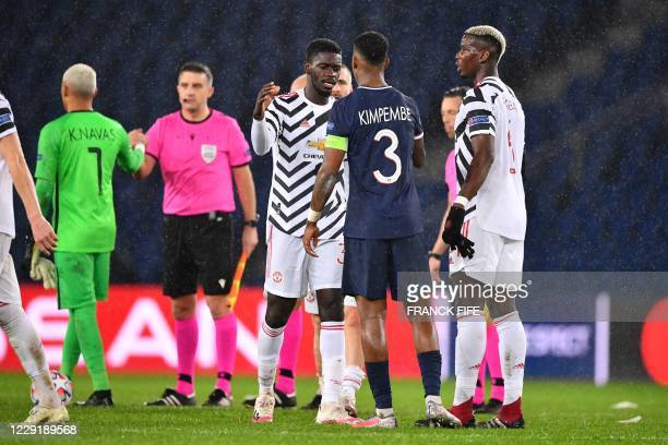 Paris Saint-Germain's French defender Presnel Kimpembe shakes hands with Manchester United's English defender Axel Tuanzebe and Manchester United's...